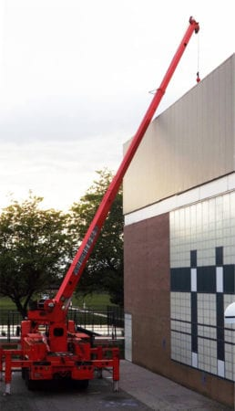 Crane loading roofing materials on the commercial building