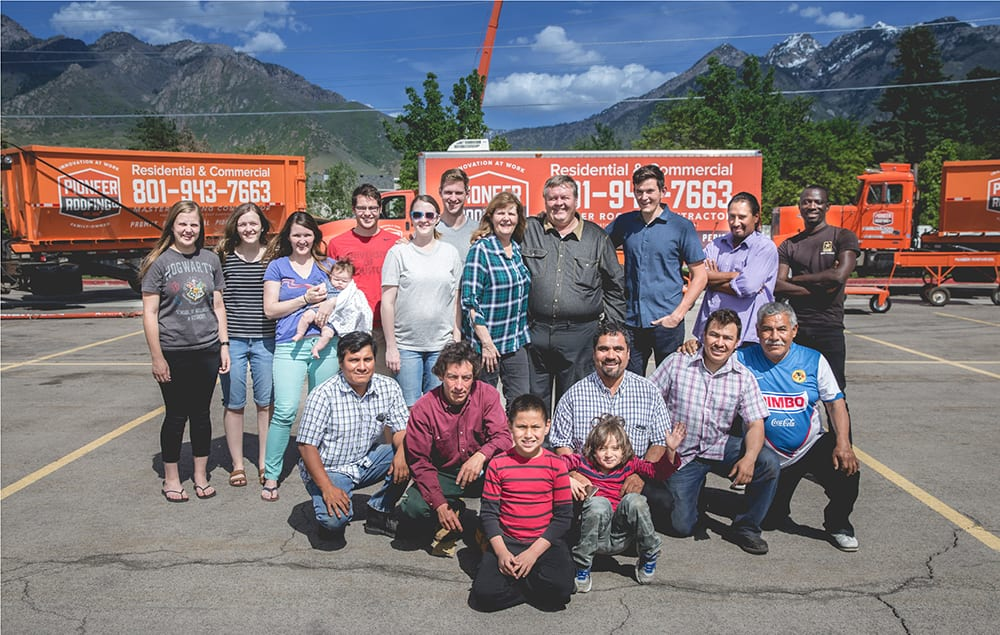The whole family standing together in the roofing materials parking lto